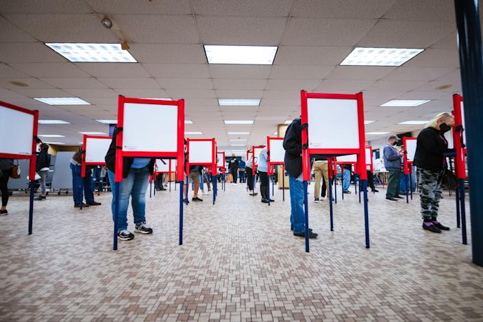 Voters stand at ballot boxes and cast their votes at Fairdale High School on Nov. 3, 2020, in Louisville. (Photo: Jon Cherry via Getty Images)