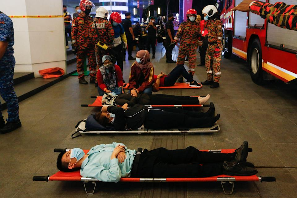 <p>Injured passengers lie on stretchers outside a Kuala Lumpur metro station after two trains collided in a tunnel on 24 May</p> (AFP/Getty)