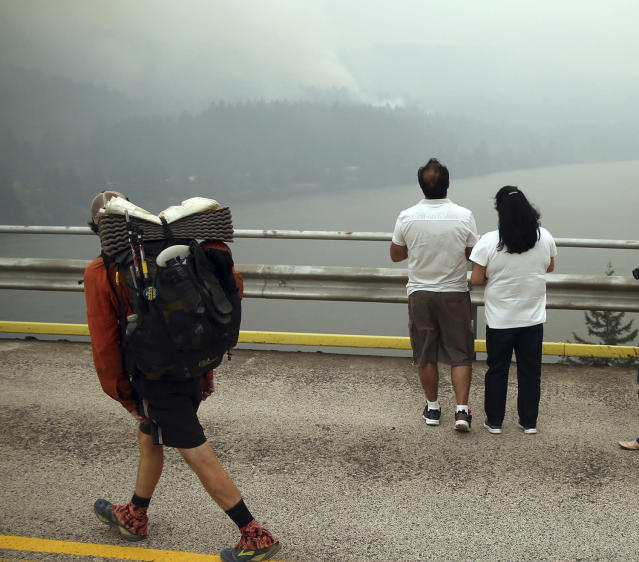 <p>A hiker and two others look at smoke from the Eagle Creek wildfire on the Oregon side of the Columbia River Gorge from the Bridge of the Gods, spanning the Columbia River between Washington and Oregon states, near Stevenson, Wash., on Sept. 6, 2017. (Photo: Randy L. Rasmussen/AP) </p>
