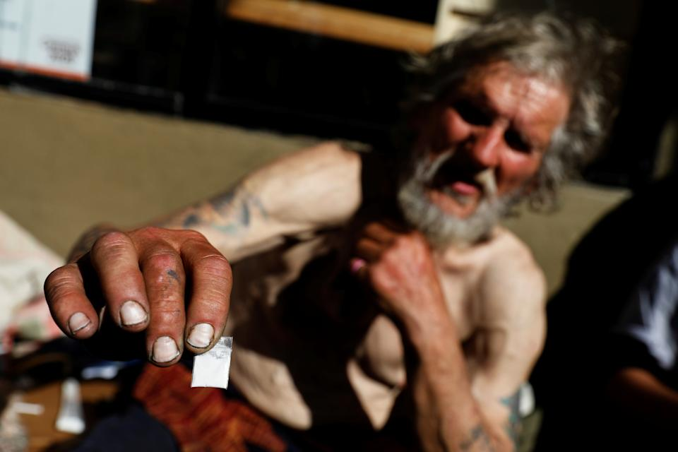 Travis Hayes, 65, holds up a bag of what he says is the synthetic drug fentanyl, across the street from where San Francisco mayor London Breed just held a news conference introducing legislation in curbing the rise of deadly overdoses in the city, at the Tenderloin section of San Francisco, California, U.S., February 27, 2020.   REUTERS/Shannon Stapleton