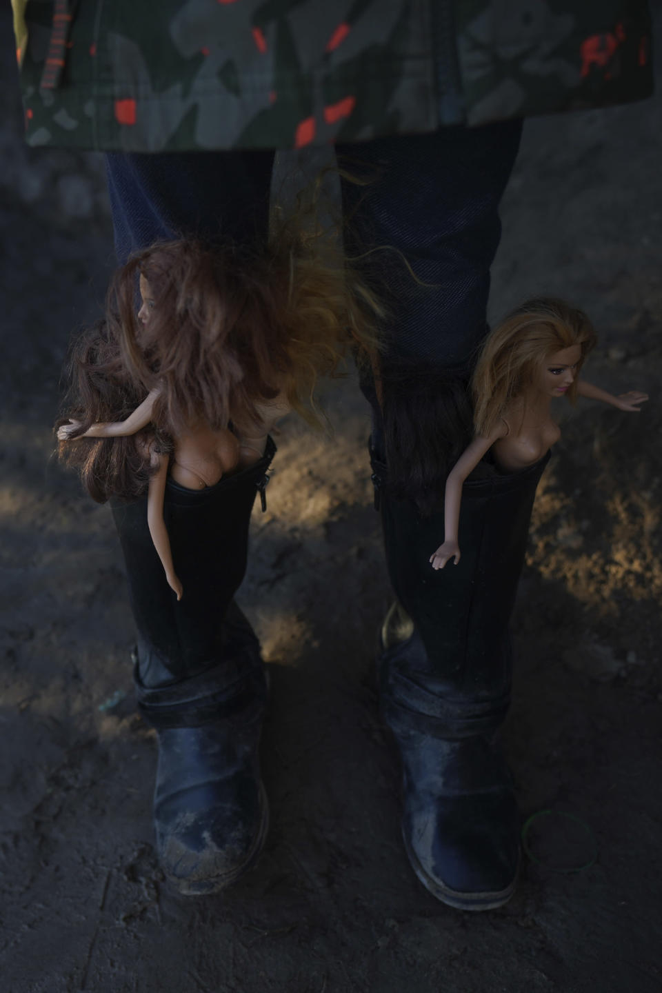 A girl with Barbie dolls stuffed in her boots waits with other children to cross the Rio Grande river with their parents as they stand on the bank of the Rio Grande river in Ciudad Acuna, Mexico, at dawn Thursday, Sept. 23, 2021, across the border from Del Rio, Texas. (AP Photo/Fernando Llano)