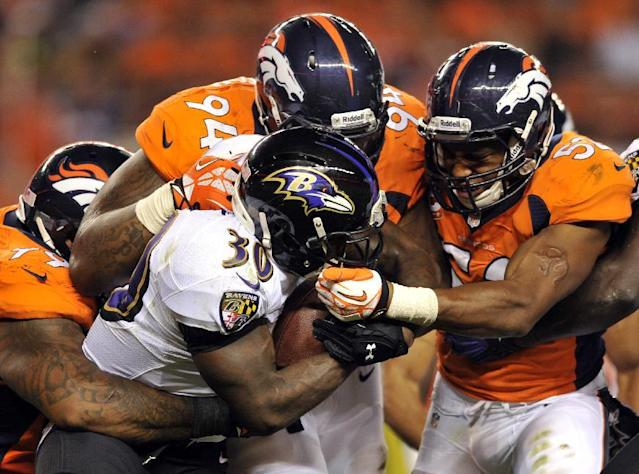 FILE - In this Sept. 25, 2013 file photo, Baltimore Ravens running back Bernard Pierce (30) is gang tackled by Denver Broncos defensive tackle Kevin Vickerson (99) , Terrance Knighton (94) and Wesley Woodyard (52) during an NFL football game, in Denver. Increasingly, teams are having trouble getting what they need on the ground on third or fourth down, with 2 or fewer yards needed for a first down or a touchdown. And increasingly, they're trying to pass for those short gains. (AP Photo/Jack Dempsey, File)