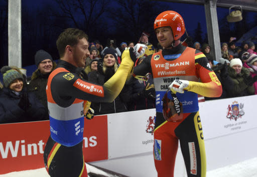 Toni Eggert and Sascha Benecken of Germany celebrate after finishing first in a men's doubles race at the Luge World Cup event in Sigulda, Latvia, Saturday, Jan. 12, 2019. (AP Photo/Roman Koksarov)
