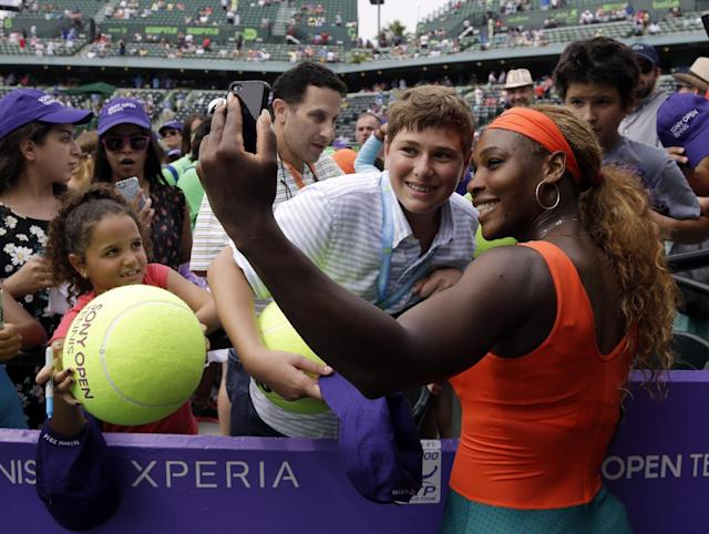 "Serena Williams, right, takes a ""selfie"" photo with a fan following her 7-5, 6-1 victory over Li Na, of China, during the women's final at the Sony Open Tennis tournament, Saturday, March 29, 2014, in Key Biscayne, Fla. (AP Photo/Alan Diaz)"