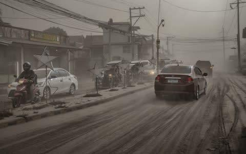 <span>Residents in the town of Lemery attempt to carry on with everyday life as ash carpets the streets</span> <span>Credit: Ezra Acayan/Getty Images </span>