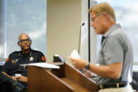 Waterloo Police Chief Joel Fitzgerald, left, listens to Cedar Valley Backs the Blue chairman Lynn Moller speak during a City Council meeting, Tuesday, Sept. 7, 2021, in Waterloo, Iowa. Fitzgerald, the first Black police chief in Waterloo, is facing intense opposition from some current and former officers as he works with city leaders to reform the department, including the removal of its longtime insignia that resembles a Ku Klux Klan dragon. (AP Photo/Charlie Neibergall)