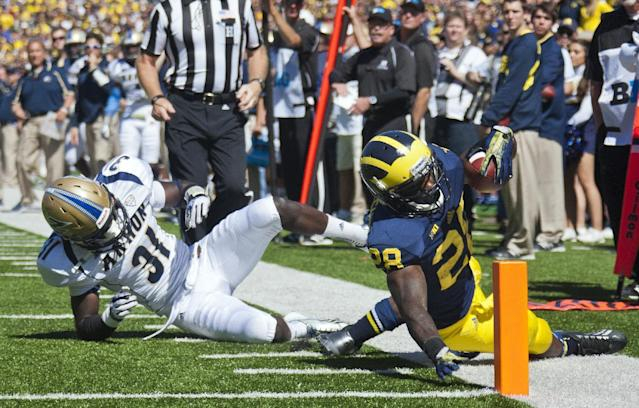 Michigan running back Fitzgerald Toussaint (28) dives toward the pylon ahead of Akron cornerback Emmanuel Lartey (31) in the second quarter of an NCAA college football game, Saturday, Sept. 14, 2013, in Ann Arbor, Mich. The play was called back due to a Michigan penalty. (AP Photo/Tony Ding)