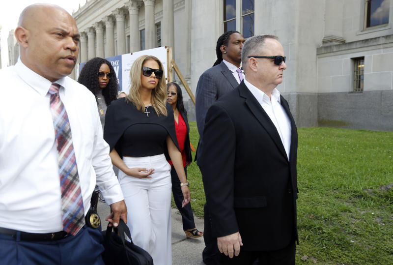 Racquel Smith, center, widow of former New Orleans Saints star Will Smith, leaves Orleans Parish criminal courthouse Thursday, April 20, 2017, after the sentencing of Cardell Hayes, who killed her husband and shot her, and was convicted of manslaughter in New Orleans. Hayes was sentenced to 25 years in prison for manslaughter, far less than the maximum prosecutors had called for. He also received 15 years for shooting Racquel Smith in the legs, to be served at the same time. (AP Photo/Gerald Herbert)