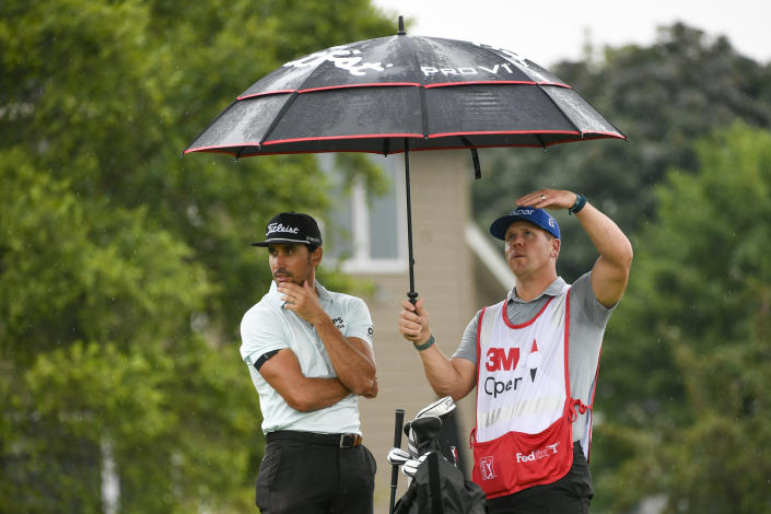 Rafa Cabrera Bello, left, waits with caddie Ben Hulka for play to resume after a rain delay at the 18th hole during the first round of the 3M Open golf tournament in Blaine, Minn., Thursday, July 22, 2021. (AP Photo/Craig Lassig)