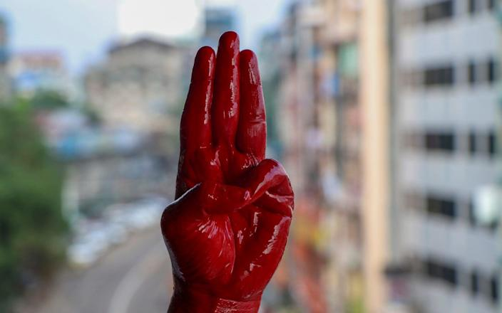 An anti-coup protester shows a three-fingered salute, hand painted red in memory of those killed - AP