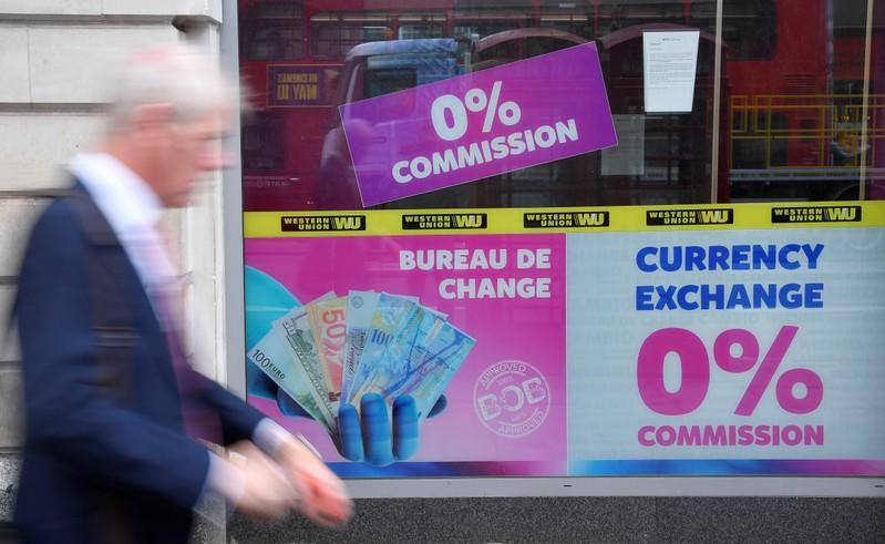 FILE PHOTO: A man walks past a currency exchange outlet in London