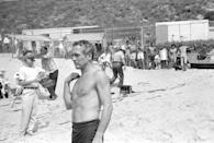<p>Paul Newman makes a movie on the beach while people watch through the fence. </p>