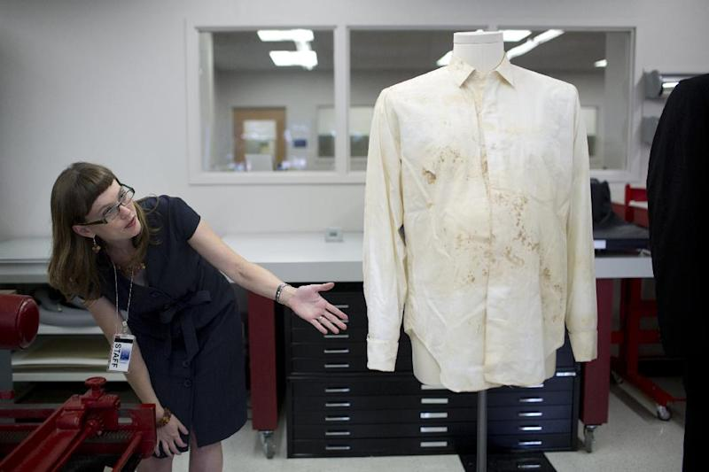 Sarah Norris, conservator for the Texas State Library and Archives Commission, points out a bullet hole in the blood-stained shirt worn by Texas Gov. John Connally on the day gunfire wounded him and killed President John F. Kennedy in Dallas, Texas on Nov. 22, 1963, at the Texas State Library and Archives Commission in Austin, Texas on Tuesday, Oct. 15, 2013. Texas state archivists are preparing the suit and shirt worn by Connally as the centerpiece for an exhibit to mark next month's 50th anniversary of Kennedy's assassination. (AP Photo/Tamir Kalifa)