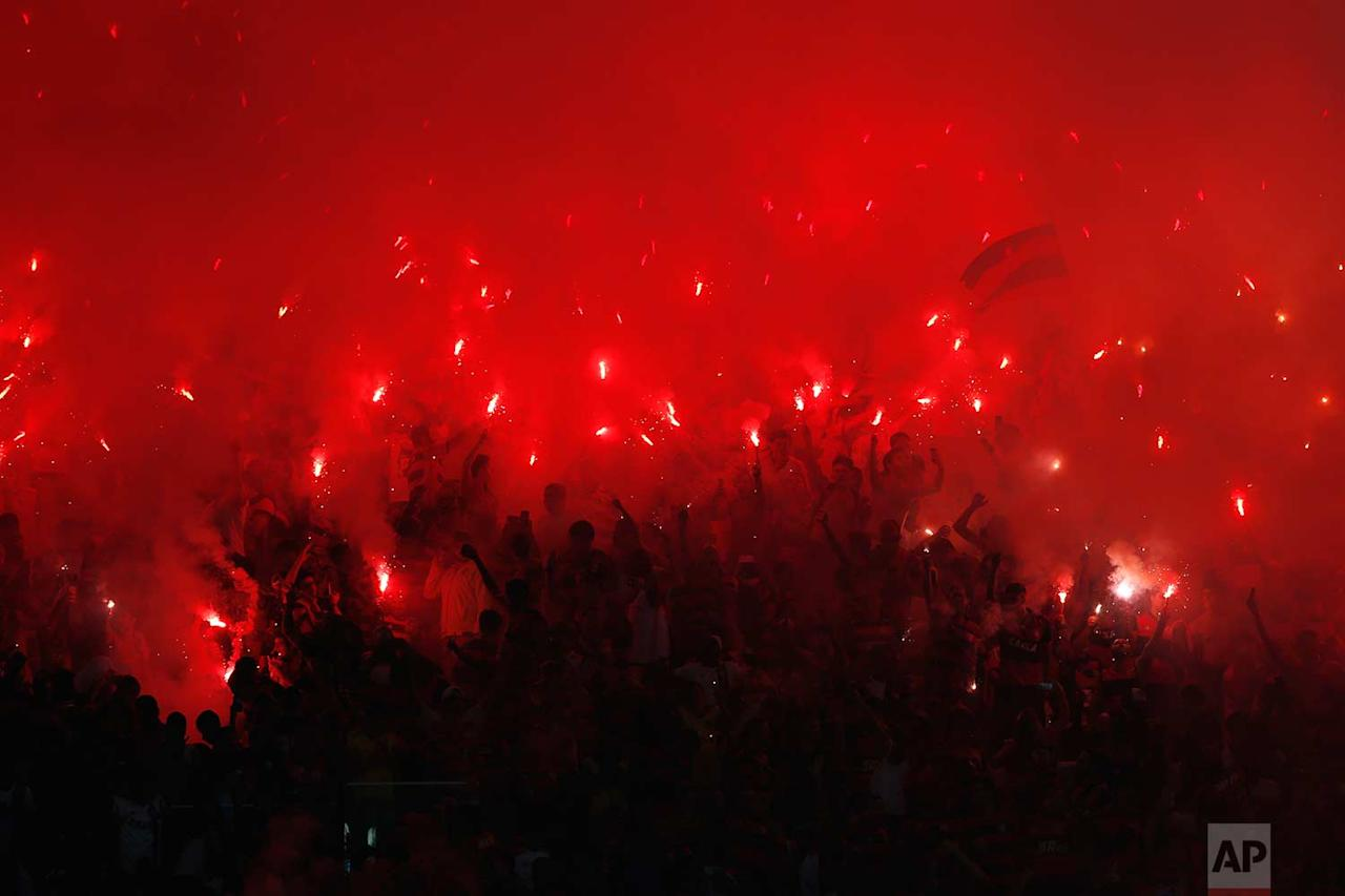<p>Fans of Brazil's Flamengo soccer team light flares in the stands during a Copa Sudamericana final championship soccer match against Argentina's Independiente at Maracana stadium in Rio de Janeiro, Brazil. (AP Photo/Silvia Izquierdo) </p>