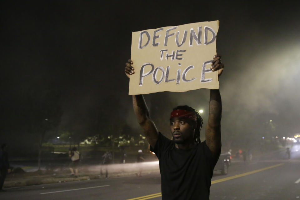 A man holds up a sign amid smoke of a fire during a protest Saturday, June 13, 2020, near the Atlanta Wendy's where Rayshard Brooks was shot and killed by police Friday evening following a struggle in the restaurant's drive-thru line in Atlanta. (AP Photo/Brynn Anderson)