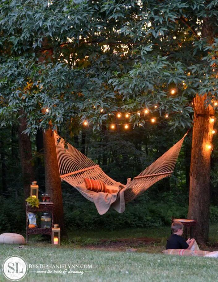 """<p>Is there anything more soothing than a hammock gently swinging under string lights? This easy-to-pull-off setup is guaranteed to be your favorite spot to relax.</p><p><strong>Get the tutorial at <a href=""""http://www.bystephanielynn.com/2013/06/backyard-hammock.html"""" rel=""""nofollow noopener"""" target=""""_blank"""" data-ylk=""""slk:By Stephanie Lynn"""" class=""""link rapid-noclick-resp"""">By Stephanie Lynn</a>.</strong></p><p><strong><a class=""""link rapid-noclick-resp"""" href=""""https://www.amazon.com/Backyard-Hanging-Outdoor-Pergola-Deckyard/dp/B00RQHBZVS?tag=syn-yahoo-20&ascsubtag=%5Bartid%7C10050.g.3404%5Bsrc%7Cyahoo-us"""" rel=""""nofollow noopener"""" target=""""_blank"""" data-ylk=""""slk:SHOP STRING LIGHTS"""">SHOP STRING LIGHTS</a><br></strong></p>"""