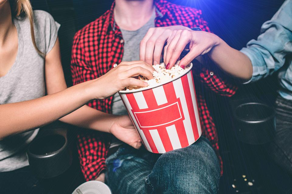 Close up of red with white basket of popcorn that both girl and guy are holding. All of them are taking popcorn out of basket. Ð¡ut view