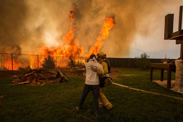 <p>A firefighter consoles a man who is worried that his sister's house (R) will burn during the Holy Fire in Lake Elsinore, Calif., Aug. 9, 2018. (Photo: David McNew/EPA-EFE/REX/Shutterstock) </p>