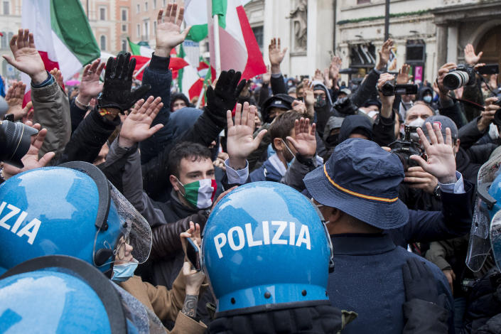 """Demonstrators of the """"Io apro"""" (I open) movement face police during a protest against restriction measures to curb the spread of COVID-19, in Rome, Monday, April 12, 2021. Italian restaurant owners from all over Italy and others angry at having their businesses shut for weeks due to a virus lockdown scuffled with police Monday during a non-authorized protest nearby the Parliament in Rome. (Roberto Monaldo/LaPresse via AP)"""