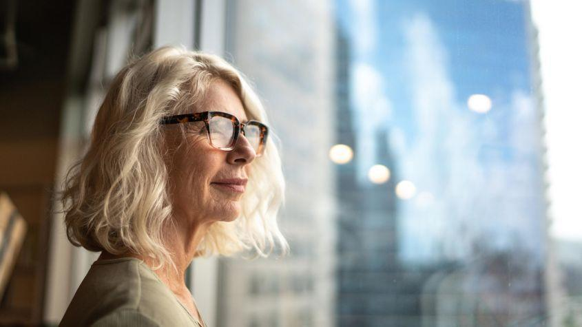 An older woman looks out a window.