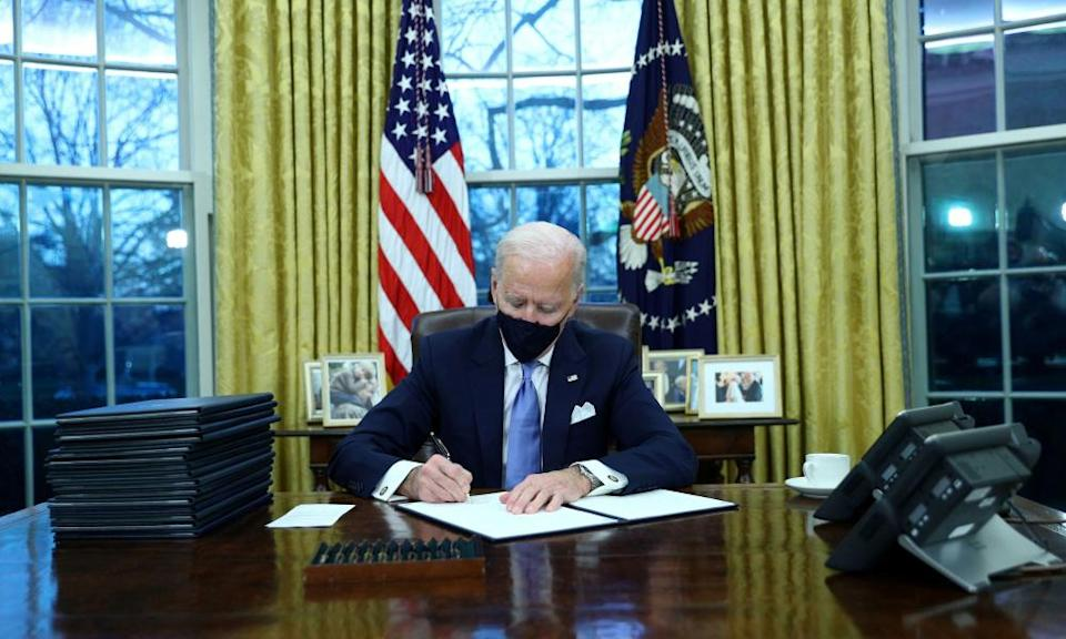 Joe Biden signs executive orders in the Oval Office after his inauguration.