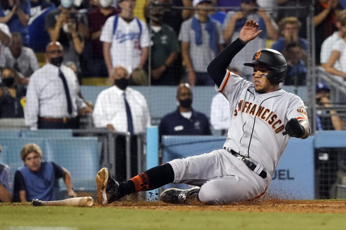 San Francisco Giants' Thairo Estrada scores on a single by LaMonte Wade Jr. during the ninth inning of the team's baseball game against the Los Angeles Dodgers on Thursday, July 22, 2021, in Los Angeles. (AP Photo/Marcio Jose Sanchez)
