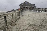 High winds blow sea foam onto Jeanette's Pier in Nags Head, N.C., Sunday, Oct. 28, 2012 as wind and rain from Hurricane Sandy move into the area. Governors from North Carolina, where steady rains were whipped by gusting winds Saturday night, to Connecticut declared states of emergency. Delaware ordered mandatory evacuations for coastal communities by 8 p.m. Sunday. (AP Photo/Gerry Broome)