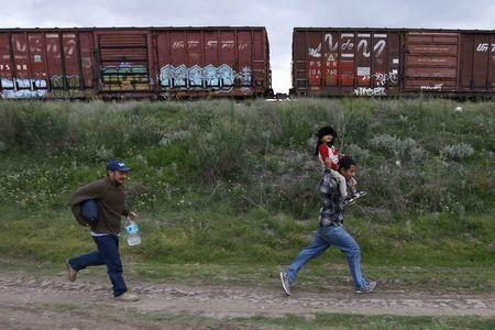A Salvadoran father (R) carries his son while running next to another immigrant as they try to board a train heading to the Mexican-U.S. border, in Huehuetoca, near of Mexico City, June 1, 2015. REUTERS/Edgard Garrido/File Photo