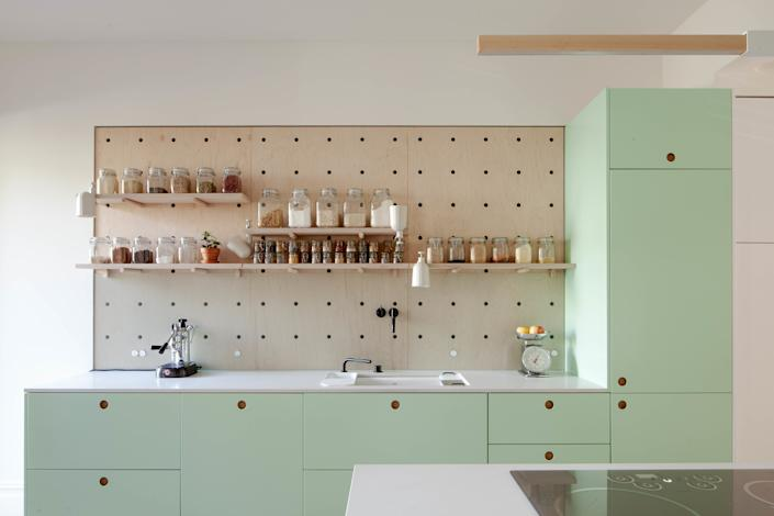 "<div class=""caption""> The kitchen cabinets are Reform fronts on IKEA boxes. The mint-green color was matched to a favorite set of pendant lights, and the fridge is hidden behind the tall cabinets at right. </div> <cite class=""credit"">Peter Dressel 2018</cite>"