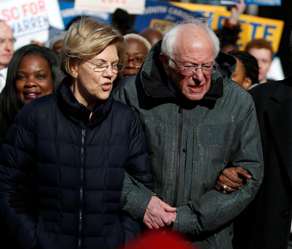 Seven of the Democratic US Presidential candidates including U.S. Senator Elizabeth Warren and Sen. Bernie Sanders, walk arm-in-arm with local African-American leaders during the Martin Luther King Jr. (MLK) Day Parade in Columbia, South Carolina, U.S. January 20, 2020.  REUTERS/Randall Hill