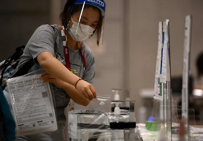 A journalist wearing a facemask as a preventive measure against the Covid-19 coronavirus drops her daily saliva sample for PCR test at the media centre ahead of the opening of the Tokyo 2020 Olympic Games in Tokyo on July 20, 2021.