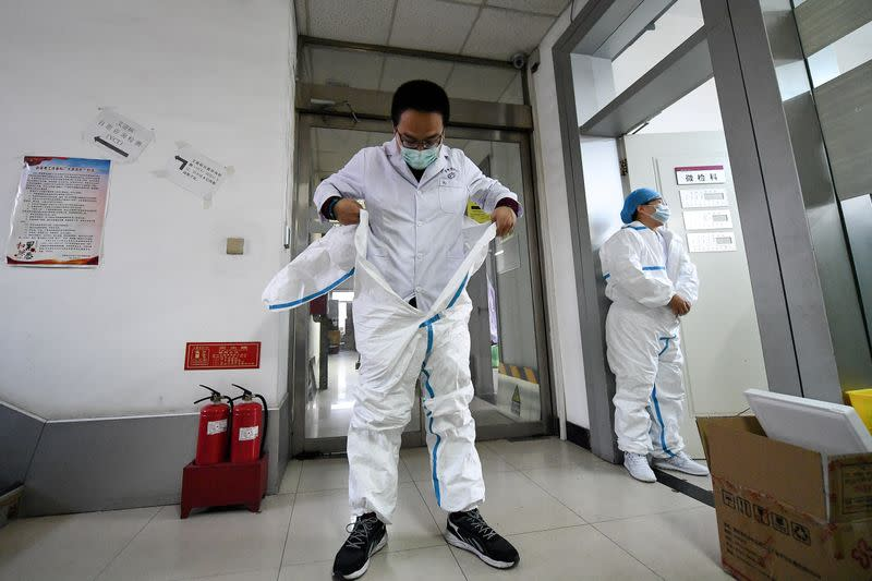 Worker puts on his protective suit before entering a laboratory at a centre for disease control and prevention in Taiyuan