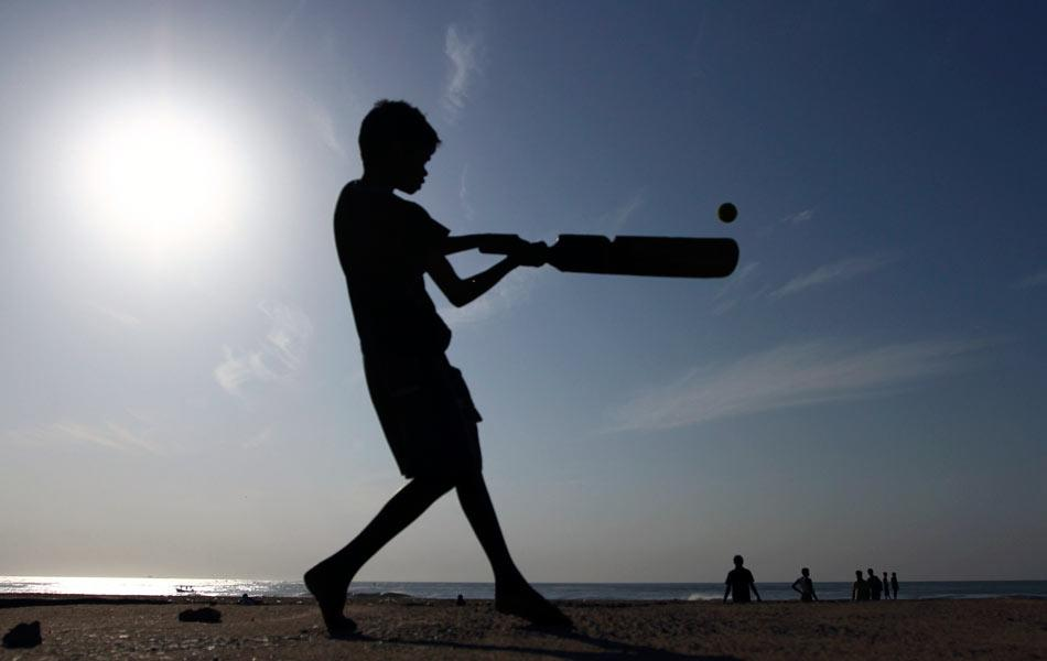 A boy plays cricket in the early morning on the Marina beach at the southern Indian city of Chennai June 23, 2012. REUTERS/Babu