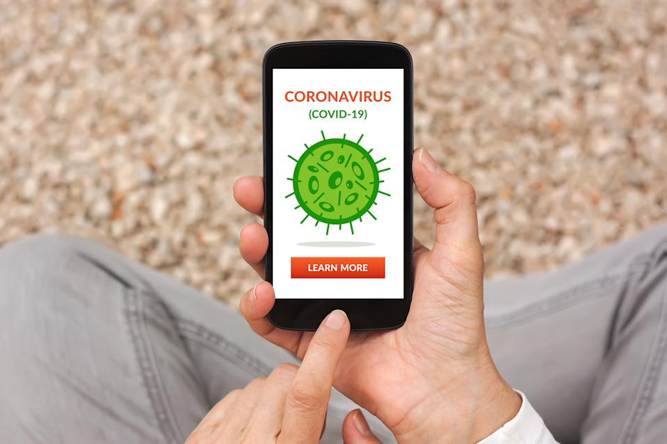 Hands holding smart phone with coronavirus, covid-19 concept on screen. Social distancing. Top view
