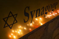 FILE - In this Friday, Oct. 11, 2019 file photo, candles reflect in an entrance sign after a human chain with lights was formed around the Jewish synagogue during the Sabbath celebrations in Halle (Saale), Germany, following an attack on the synagogue on Yom Kippur 2019. As Jews around the world gather Sunday night to mark the beginning of Yom Kippur, many in Germany remain uneasy about going together to their houses of worship to pray, a year after a white-supremacist targeted a synagogue in the eastern city of Halle on the holiest day in Judaism. (AP Photo/Jens Meyer, file)