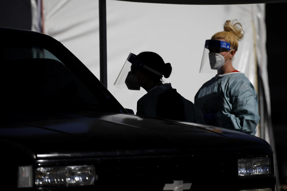FILE - In this July 10, 2020, file photo, healthcare workers test patients in their cars at a drive-thru coronavirus testing site run by the University of Nevada Las Vegas School of Medicine and the Nevada National Guard in Las Vegas. Nevada this week became one of the last states to include rapid antigen tests in its coronavirus tallies. Experts say the change could provide a fuller picture of the pandemic but also upend metrics used to gauge how the virus is spreading. Health officials say they weren't added earlier because their limited resources and staff had focused on vaccines and contact tracing confirmed cases.(AP Photo/John Locher, File)