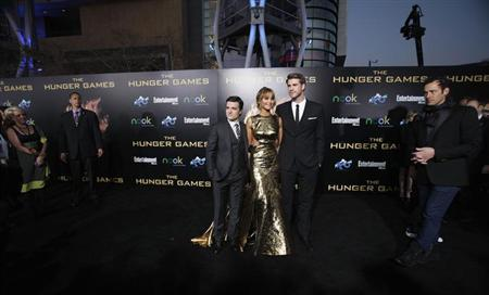 """Cast members Liam Hemsworth (R), Jennifer Lawrence and Josh Hutcherson pose at the premiere of """"The Hunger Games"""" at Nokia theatre in Los Angeles, California March 12, 2012. REUTERS/Mario Anzuoni/Files"""