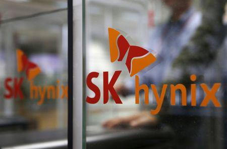 Employee walks past the logo of SK Hynix at its headquarters in Seongnam