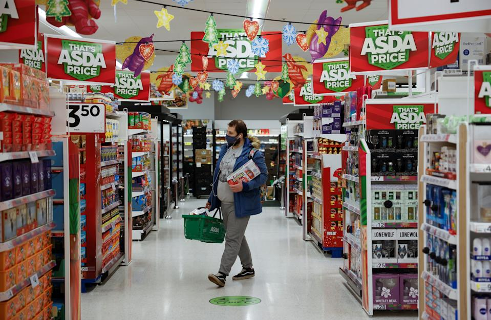 A shopper wearing a face mask or covering due to the COVID-19 pandemic, carries goods in a shopping basket inside an ASDA supermarket in Walthamstow in north east London on December 22, 2020. - The British government said Tuesday it was considering tests for truckers as part of talks with French authorities to allow the resumption of freight traffic suspended due to a new strain of coronavirus. Britain was plunged into fresh crisis last week with the emergence of a fresh strain of the virus, which is believed to be up to 70 percent more transmissible than other forms. (Photo by Tolga Akmen / AFP) (Photo by TOLGA AKMEN/AFP via Getty Images)