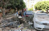 People are seen near rubble and damaged vehicles following Tuesday's blast in Beirut's port area