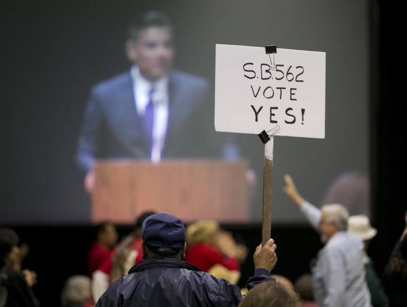 A supporter of SB562. s single-payer health care bill, holds up his sign as one of the bill's co-authors, state Sen. Ricardo Lara, D-Bell Garden, is seen on a large screen at a rally Wednesday, April 26, 2017, in Sacramento, Calif. SB562 by Lara, and Sen. Toni Atkins, D-San Diego, that would guarantee health coverage with no out-of-pocket cost for all California residents, including people living in the country illegally is to be heard in the Senate Health Committee, Wednesday. (AP Photo/Rich Pedroncelli)