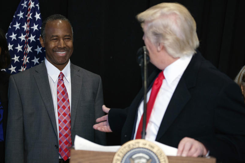 FILE - In this Feb. 21, 2017, file photo, then-Housing and Urban Development Secretary-designate Dr. Ben Carson, listens as President Donald Trump speaks after touring the National Museum of African American History and Culture in Washington. Carson's story of growing up in a single-parent household and climbing out of poverty to become a world-renowned surgeon was once ubiquitous in Baltimore, where Carson made his name. But his role in the Trump Administration has added a complicated epilogue, leaving many who admired him feeling betrayed, unable to separate him from the politics of a president widely rejected by African Americans in Baltimore. (AP Photo/Evan Vucci, File)