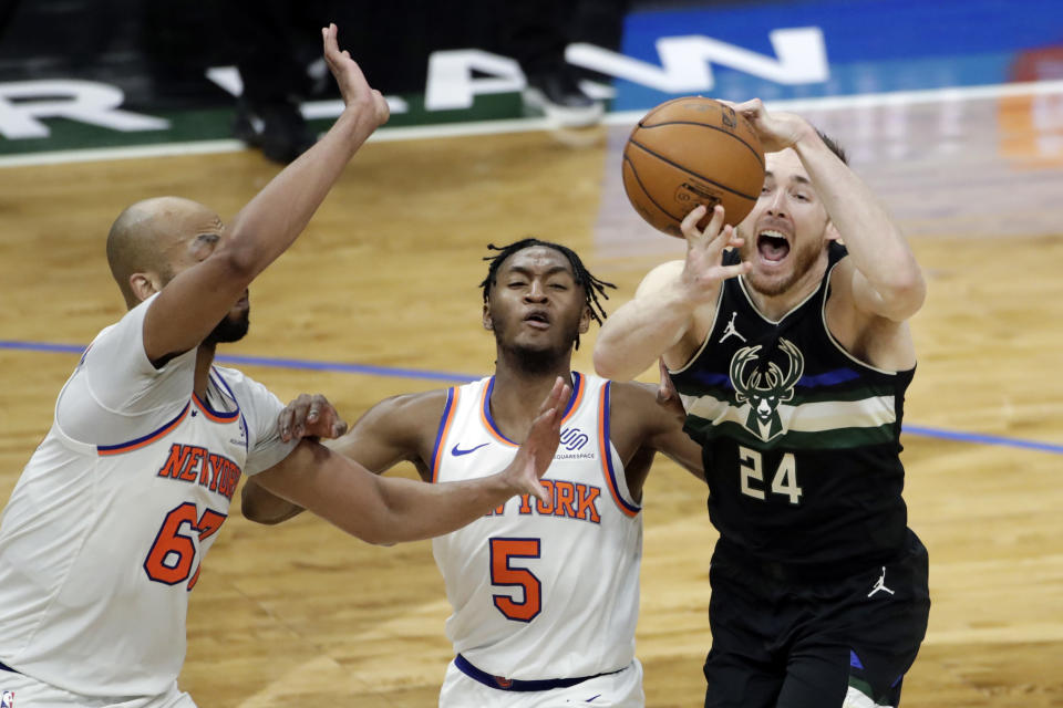 Milwaukee Bucks' Pat Connaughton (24) controls the ball as he drives to the basket against New York Knicks' Immanuel Quickley (5) and Taj Gibson (67) during the second half of an NBA basketball game Saturday, March 27, 2021, in Milwaukee. (AP Photo/Aaron Gash)