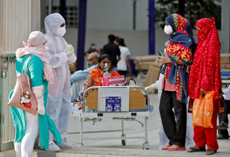 Patients sit on bed waiting to be shifted to a hospital, amidst the spread of the coronavirus disease (COVID-19) in Ahmedabad