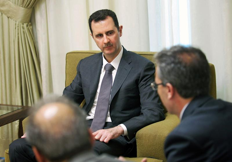 """In this photo released by the Syrian official news agency SANA, Syrian President Bashar Assad, center, speaks during an interview published with the state-run Al-Thawra newspaper, in Damascus, Syria, Thursday, July 4, 2013. Assad said that countries conspiring against Syria have """"used up all their tools"""" in their campaign to overthrow his regime and rejected the idea that what has been happening in Syria since more than two years is a revolution. (AP Photo/SANA)"""