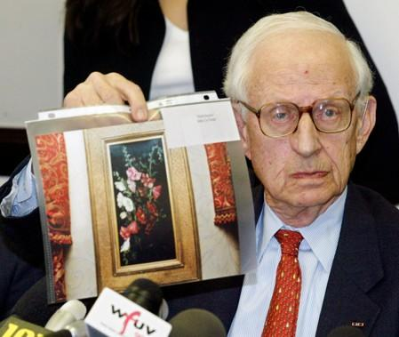 """FILE PHOTO - Manhattan District Attorney Robert Morgenthau displays a photo of the painting """"Hollyhocks"""" by John LaFarge at a press conference in New York"""