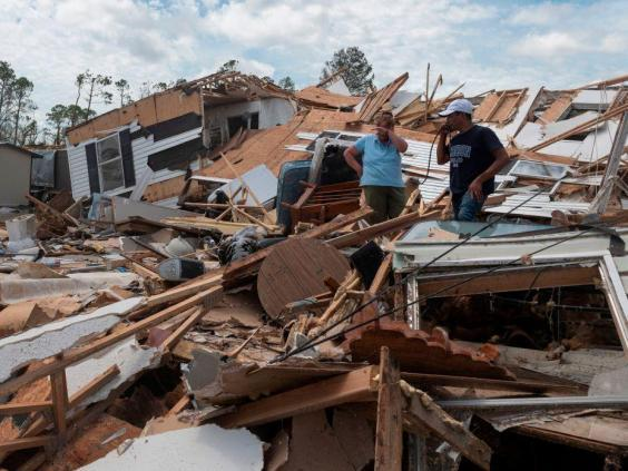 (AFP via Getty Images) Residents in Louisiana survey the wreckage of their home following Hurricane Laura this week