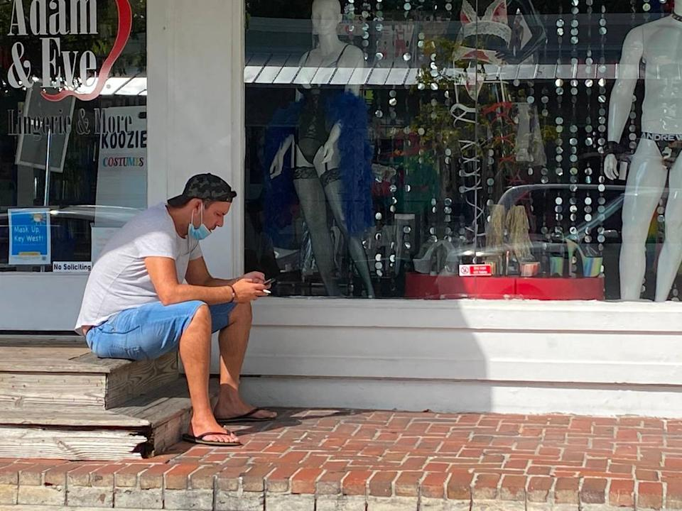 Masks are now required to be worn outside in public in the city of Key West. A man takes a cigarette break while sitting outside a closed retail shop on Duval Street on July 16, 2020.