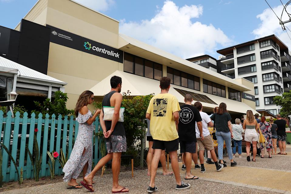 GOLD COAST, AUSTRALIA - MARCH 23: People queue outside Centrelink in Pam Beach on March 23, 2020 in Gold Coast, Australia. From midday Monday, venues such as bars, clubs, nightclubs, cinemas, gyms and restaurants, along with anywhere people remain static would be closed. Schools remain open but parents have the option to keep children at home if they wish while Victoria is bringing forward school holidays from Tuesday. There are now 1353 confirmed cases of COVID-19 In Australia and the death toll now stands at seven. (Photo by Chris Hyde/Getty Images)