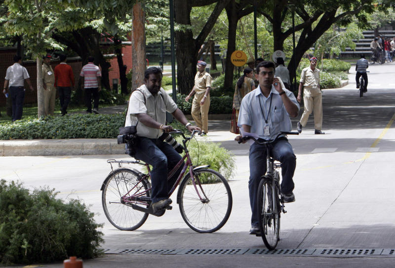 FILE - In this June 6, 2008 file photo, visitors and employees of Infosys Technologies ride bicycles inside the company's campus at Electronic City in Bangalore, India. Low cost efficiency put India's outsourcing companies at the heart of global business and created a multibillion dollar industry that for years has skated over criticism it was eliminating white collar jobs in rich nations. Now, the industry's long-held fears of a backlash are being realized in its crucial U.S. market. Provisions in an overhaul of U.S. immigration law will close loopholes that allow outsourcing companies, Indian and American, to pay guest workers in the U.S. at rates often below wages for equivalent-level Americans. (AP Photo/Aijaz Rahi, File)